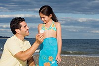 Hispanic father and daughter looking at seashell