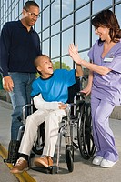 African boy in wheelchair high-fiving nurse in front of hospital