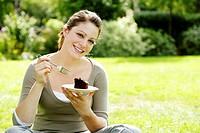 Teenage girl sitting on the field enjoying a piece of cake