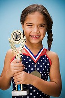 Hispanic girl smiling with medal and trophy