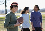 Hispanic boy holding football outdoors
