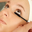 Hand curling up woman´s eyelash with a mascara wand