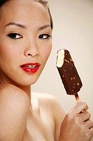Young woman enjoying a stick of chocolate ice-cream