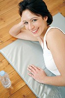 Woman lying on yoga mat