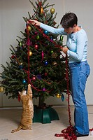 Woman playing with cat in front of Christmas tree