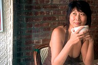 Asian woman having a cup of coffee