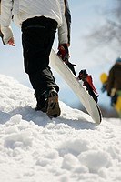 Snowboarder carrying snowboard up hill