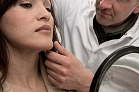 Doctor examining Asian woman´s face