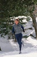 Woman jogging through snow