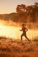 Woman jogging through meadow