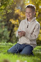 Young boy listening to mp3 player outdoors
