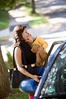 Hispanic mother carrying son to car