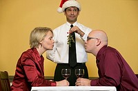 Waiter holding mistletoe for kissing couple