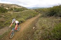 Female bicyclist on rural path