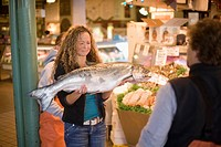 Young woman holding a large fresh fish, Pike Place Market, Seattle, Washington