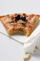 Piece of pizza with tuna and olives, a bite taken