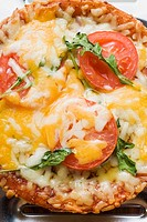 Mini-pizza with tomato, cheese and rocket