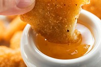 Dipping a chicken nugget in apricot sauce