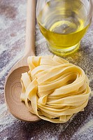 Home-made ribbon pasta with wooden spoon and olive oil