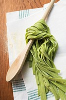 Green ribbon pasta wrapped around a wooden spoon