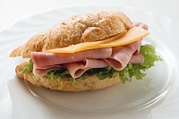 Croissant filled with ham and cheese on plate (thumbnail)