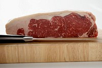A piece of beef sirloin on wooden board with knife