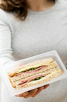 Woman holding two salami &amp; cheese sandwiches in packaging