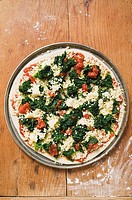Spinach, tomato and cheese pizza unbaked