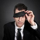 Man peeking out from under a blindfold