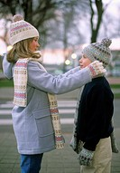 Young girl adjusting brother´s knit hat