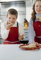 Young children eating cookies