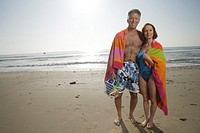 Mature couple wrapped in a towel on the beach