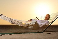 Mature man relaxing in hammock on the beach