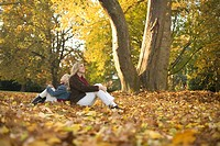 Mother and daughter sitting in park in autumn