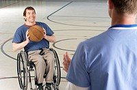 Wheelchair-bound man passing basketball to friend