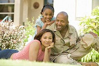 African military soldier and family in backyard
