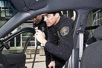 Male police officer talking into a radio
