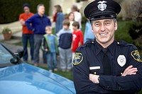 Male police officer smiling by patrol car