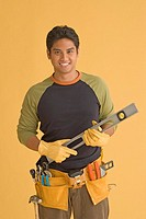 Young man wearing tool belt holding level