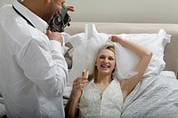 Young bride and groom filming their wedding night in bed