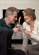 Senior couple toasting each other with wine by fireplace