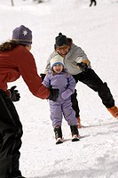 Young girl learning to ski with parents