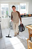 Man vacuuming kitchen floor