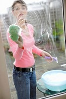 Woman cleaning glass door