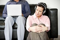 Woman listening to headphones as man uses laptop