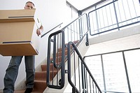 Man carrying stacked boxes down staircase