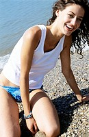 Young woman posing and laughing at beach