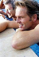 Men at edge of swimming pool smiling