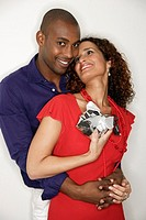 African couple hugging and holding Christmas gift