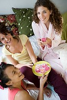 Young women wearing bathrobes with hair in rollers, eating cake